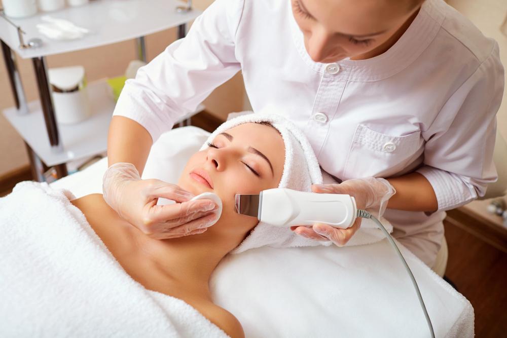 kosmetyczka wykonujaca zabiegi pielegnacyjne na twarzy kobiecie