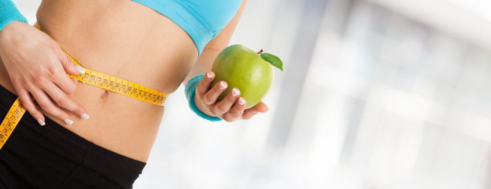 szczupła kobieta mierząca się centymetrem i trzymająca zielone jabłko w dłoni