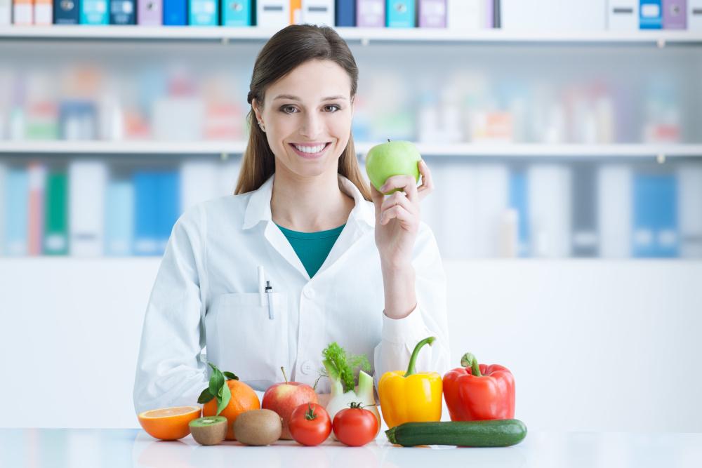 usmiechnięta pani dietetyk na której biurku znajdują się owoce i warzywa