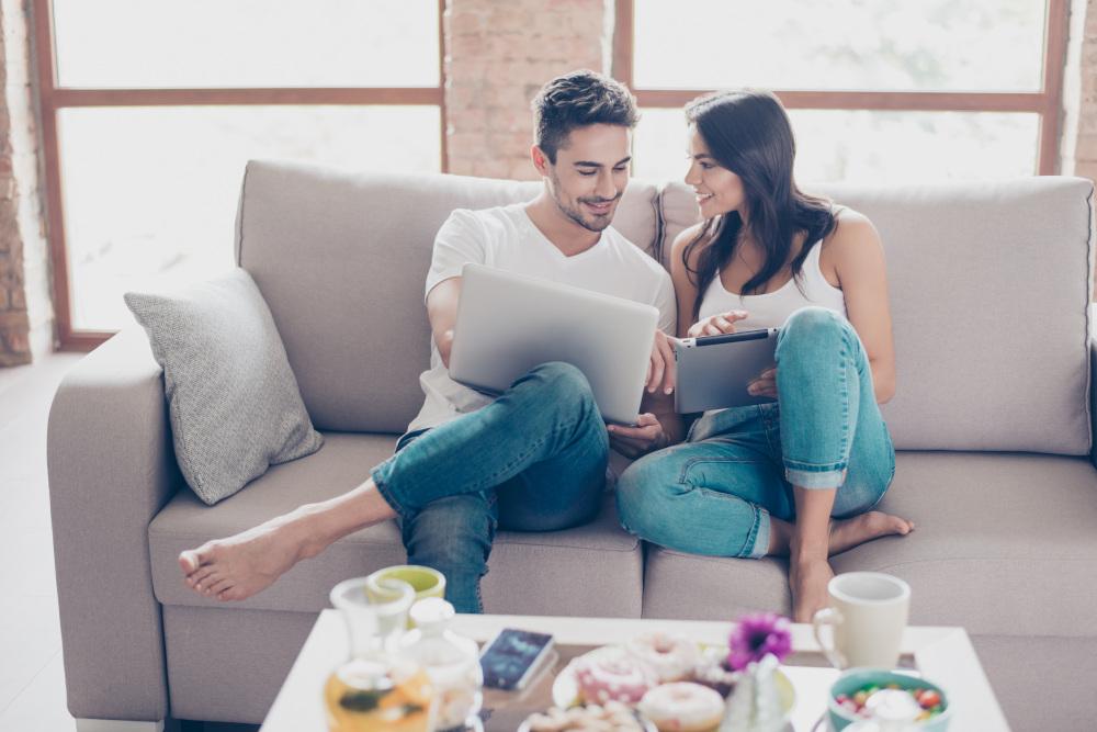 mężczyzna i kobieta siedzący na kanapie z laptopem w ręku